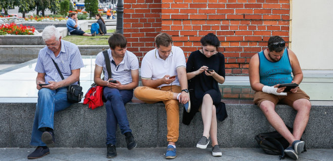 epa05492646 Ukrainians use their mobile phones as they rest during a warm and sunny summer day in downtown Kiev, Ukraine,17 August 2016. EPA/ROMAN PILIPEY